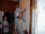 Mickey, Gary, and Jimmy hang a piece of sheetrock after tearing out the old wood siding